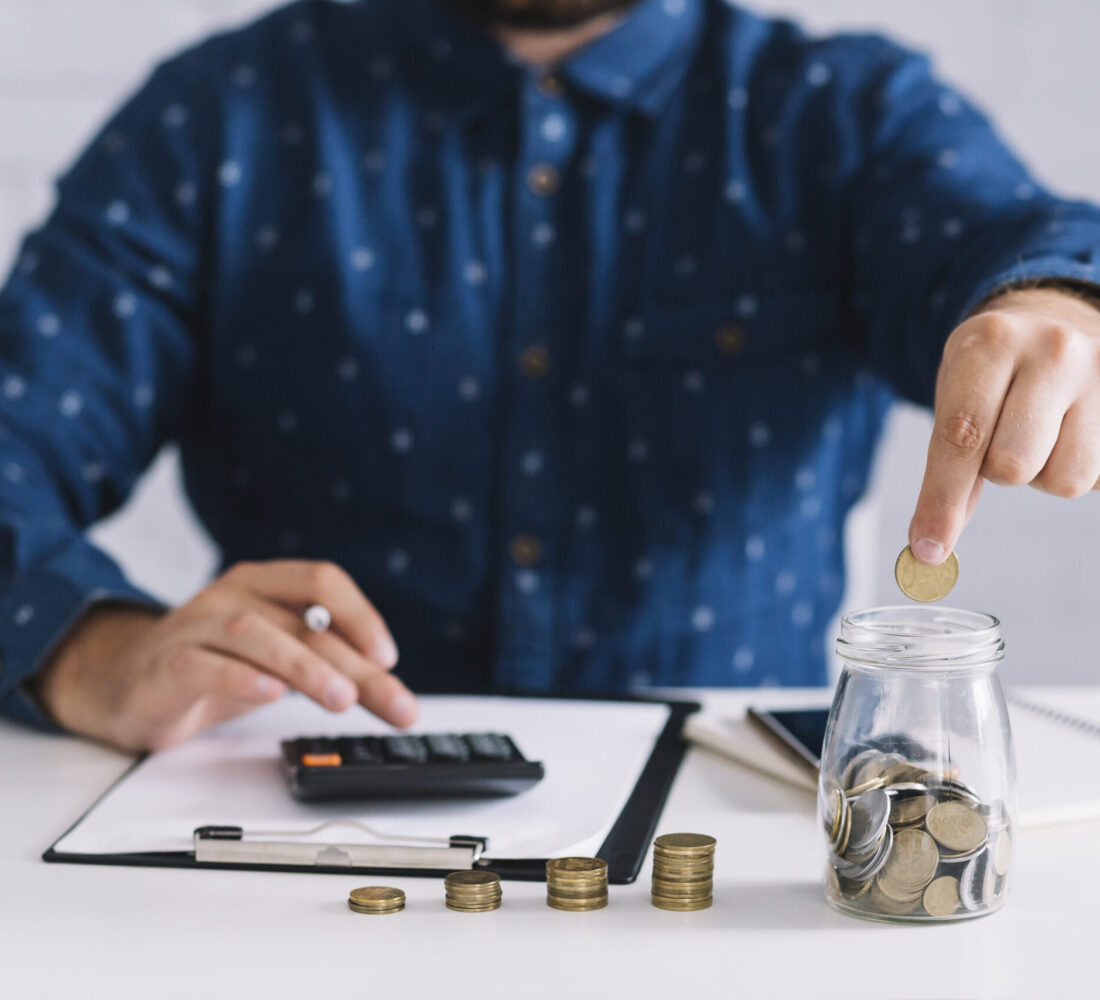 businessman-putting-coins-jar-using-calculator-workplace