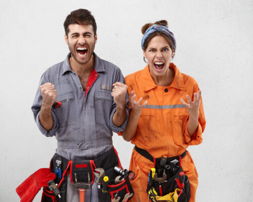 Emotional furious male and female buillders gesture angrily have irritated expressions as there is much work, being thick and tired of repairing. Tired repairman and female colleague quarrel with boss
