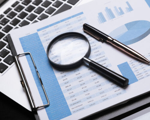 magnifying glass, documents and laptop are on table. Can be used as business background. Financier's workplace
