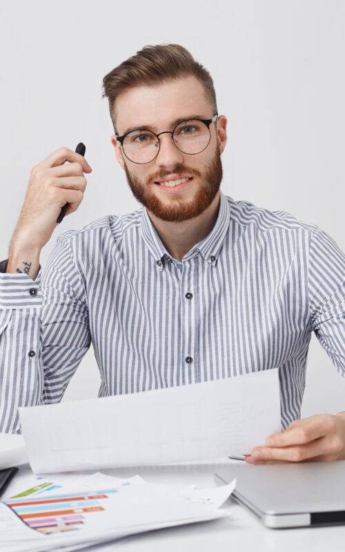 Successful professional male enterpreneur holds paper and pen, reads attentively contract, going to sign it, sits at cozy office. Berded businessman in round spectacles studies documents indoors